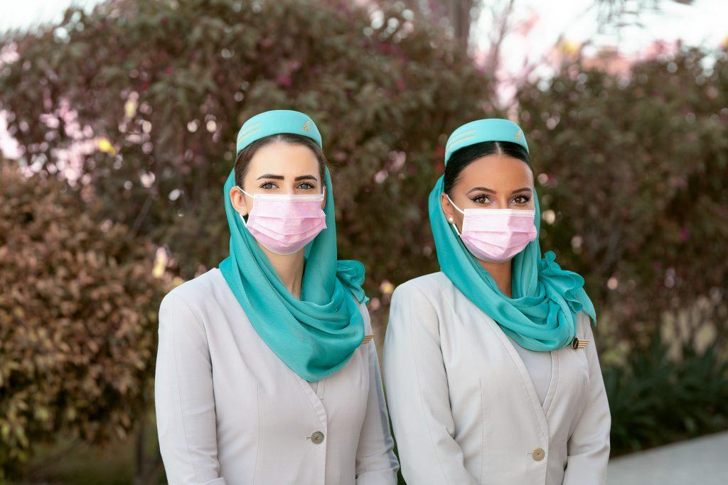 Gulf Air flight attendants wearing pink masks